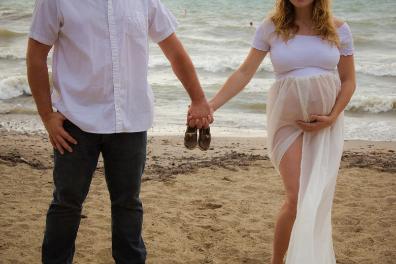 Couple holding infant shoes on beach in maternity gown